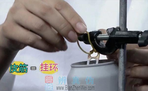 用水可迅速捏瘪易拉罐,再将准备好的皮筋穿入易拉罐的拉环里,挂在酒精灯支架上。